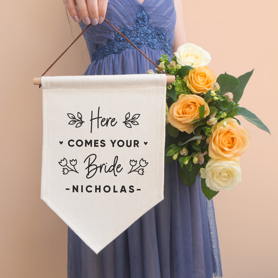 A linen pennant flag with the words 'here comes your bride [insert name of groom]. Each flag features leafy vines and little hearts. This flag has been photographed with a bridesmaid in the background wearing a purple dress and holding a peach bouquet of flowers.