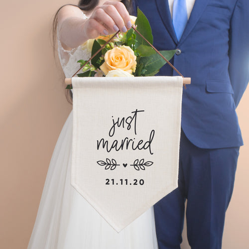 Just married personalised pennant flag with script 'just married', vine and a heart detail and a personalised wedding date. The flag is held by the bride and stood with the groom in a blue suit.