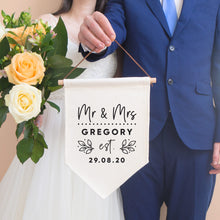 Load image into Gallery viewer, A personalised wedding pennant flag featuring your new title e.g. Mr & Mrs, your new family name and the date that you tied the knot. This linen flag is being held by the groom in a blue suit and the bride is to the left holding a bouquet of peach roses.