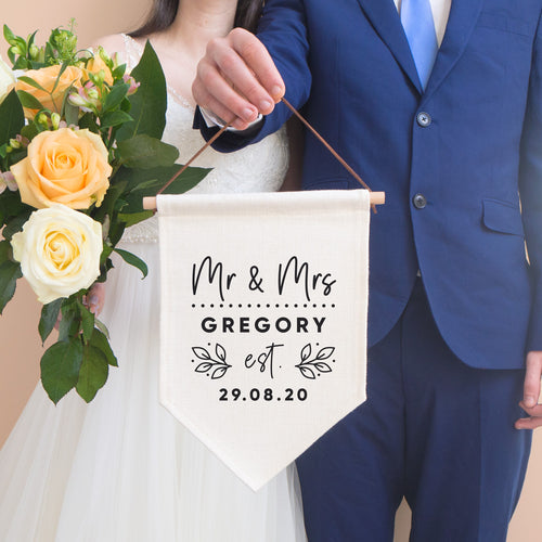 A personalised wedding pennant flag featuring your new title e.g. Mr & Mrs, your new family name and the date that you tied the knot. This linen flag is being held by the groom in a blue suit and the bride is to the left holding a bouquet of peach roses.