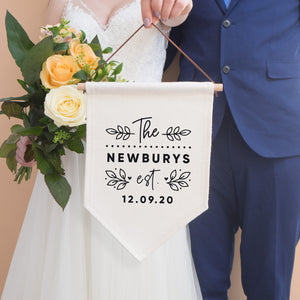 A personalised wedding pennant flag that reads' The [family name] est. [wedding date]. The text is surrounded by leafy vines and love hearts. A bride is holding the flag with a bouquet of peach flowers and is stood next to a groom in a blue suit.