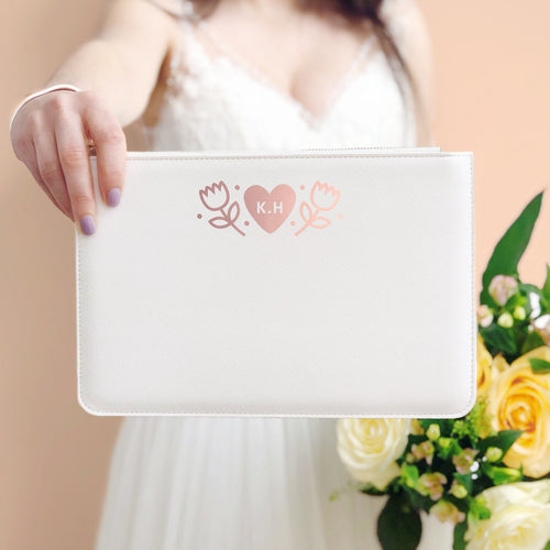 A white, personalised Bridesmaids wristlet held by Joanne Hawker in an ivory wedding dress with a bunch of peach and cream roses.