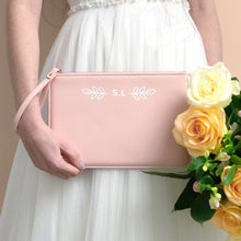 Load image into Gallery viewer, A pink, personalised Bridesmaids wristlet held by Joanne Hawker in an ivory wedding dress with a bunch of peach and creamroses.