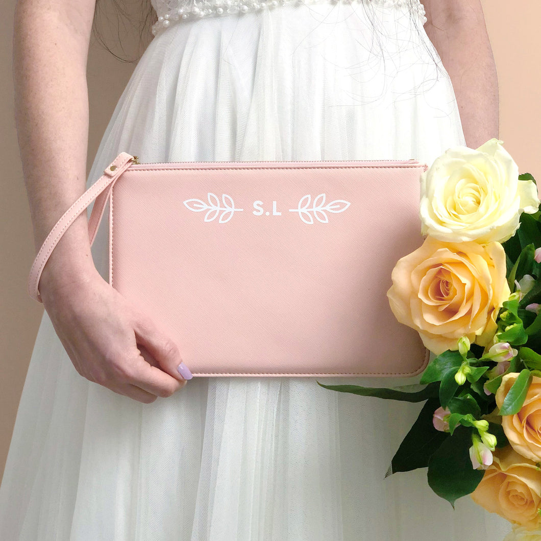 A pink, personalised Bridesmaids wristlet held by Joanne Hawker in an ivory wedding dress with a bunch of peach and creamroses.