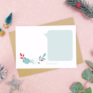 A make your own scratch card with a blank area for drawing and blank speech bubble for writing your message. Shot on pink with snow and greenery.