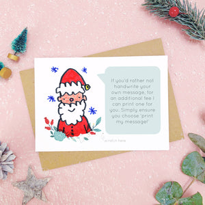 A make your own scratch card with a childs drawing of santa and an example of a printed message. Shot on pink with snow and greenery.