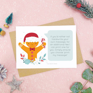A personalised gingerbread man scratch card an example of the printed message. Shot on a pink background with grey and green festive props.