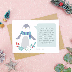 Penguin scratch card showing where you write your hidden message can be printed. Shot on a pink background, surrounded with festive christmas props in tones of green and grey.