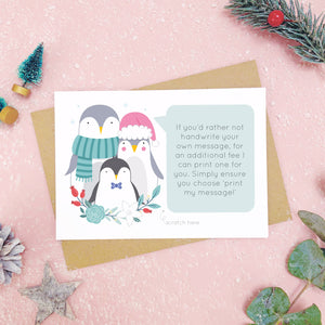 A personalised penguin family scratch card an example of the printed message. Shot on a pink background with grey and green festive props.