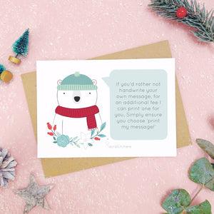 A personalised polar bear scratch card shot on a pink background with festive props in grey and green. This is an example of the printed message option.