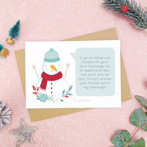 A personalised snowman scratch card an example of the printed message. Shot on a pink background with grey and green festive props.