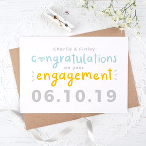 A personalised engagement card with room for the happy couples names and date the question was popped! This card has orange and blue text on a white background with a grey date.