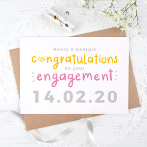 A personalised engagement card with room for the happy couples names and date the question was popped! This card has orange and pink text on a white background with a grey date.