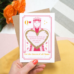 A queen of all mums scratch card showing you where your printed personalisation will go on the card. The card has been scratched off revealing the personalisations and is being held above pink tulips and a yellow skirt.