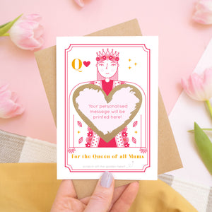 A queen of all mums scratch card showing you where your printed personalisation will go on the card. The card has been scratched off and is being held above pink tulips and a yellow skirt.