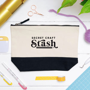 A secret craft stash cotton storage bag, natural in colour with a black box bottom base photographed in a flat lay style surrounded by craft supplies