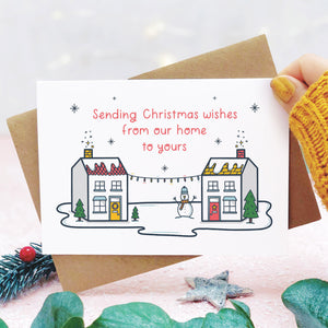 A sending wishes from our home to yours card photographed on a pink background, and being held on the right hand side with a yellow sleeve in view, with grey and green foliage. The card features two little houses connected by fairy lights.
