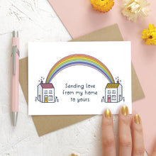 Load image into Gallery viewer, A sending love, rainbow house card photographed on a white and pink background with a pink pen, dried flowers and a hand.. The card features two houses being joined together with a pastel rainbow and text that reads 'sending love from my home to yours'.