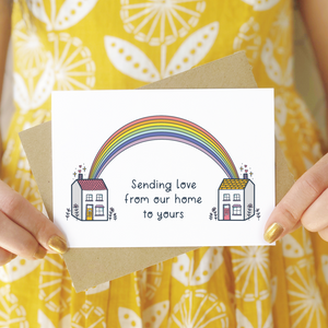 A sending love, rainbow house card photographed being held in front of a person wearing a yellow patterned dress. The card features two houses being joined together with a pastel rainbow and text that reads 'sending love from our home to yours'.