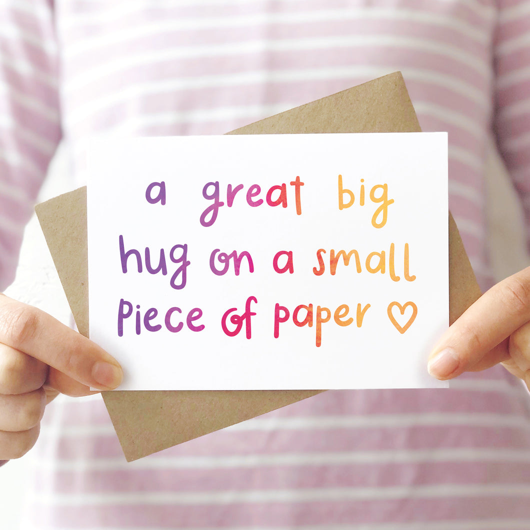 A great big hug on a small piece of paper card photographed being held in front of a pink stripey shirt.
