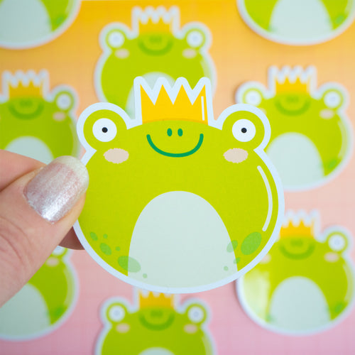 A frog sticker being held over a pink and yellow background where there are more frog stickers which are not in focus.