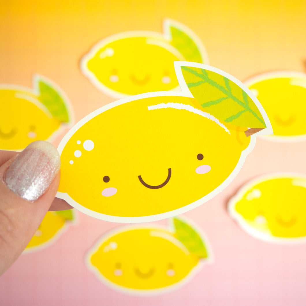 A lemon sticker being held over a pink and yellow background where there are more lemon stickers which are not in focus.