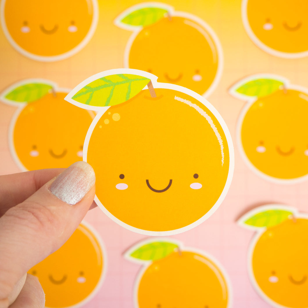 A satsuma orange sticker being held over a pink and yellow background where there are more orange stickers which are not in focus.