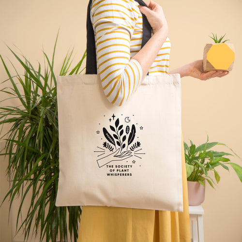 The society of plant whisperers organic cotton tote bag modelled by Joanne Hawker on a peach background. The organic tote bag has a black print and black handles.