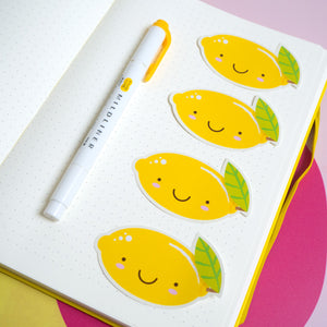 Lemon stickers laid out on a blank page in an A5 bullet journal with a mildliner pen for scale.