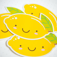 Load image into Gallery viewer, A close up of the yellow lemon sticker sat on top of a pile of lemon stickers.