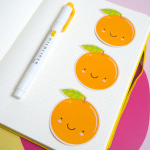 3 satsuma orange stickers laid out in a A5 bullet journal with a mildliner pen for scale.