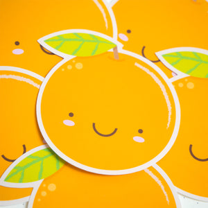 A close up of an orange satsuma sticker on top of a pile of orange stickers.