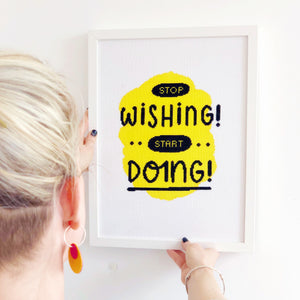 The completed stop wishing start doing modern xstitch kit in yellow and framed in a white frame