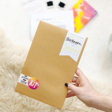 Load image into Gallery viewer, The stop wishing start doing collaboration kit comes packaged in a limited edition brown envelope.