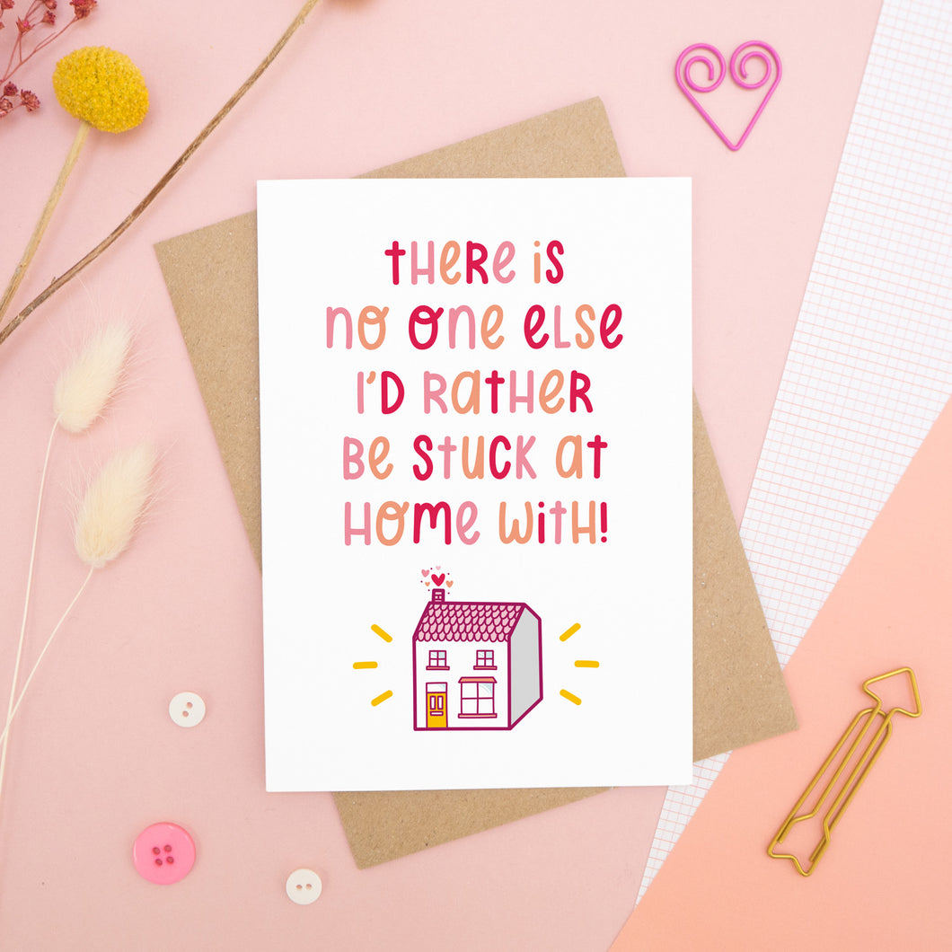 The 'stuck at home with you' card photographed on a pink background with dried flowers, buttons and paper clips as props.