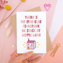 Load image into Gallery viewer, The 'stuck at home with you' card photographed on a pink background with dried flowers, buttons and paper clips as props. The card itself is being held above the scene.