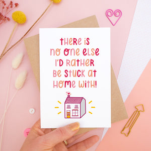 The 'stuck at home with you' card photographed on a pink background with dried flowers, buttons and paper clips as props. The card itself is being held above the scene.