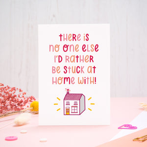 The 'stuck at home with you' card photographed standing up against an off white background with flowers, buttons and paperclips at the base of the card.