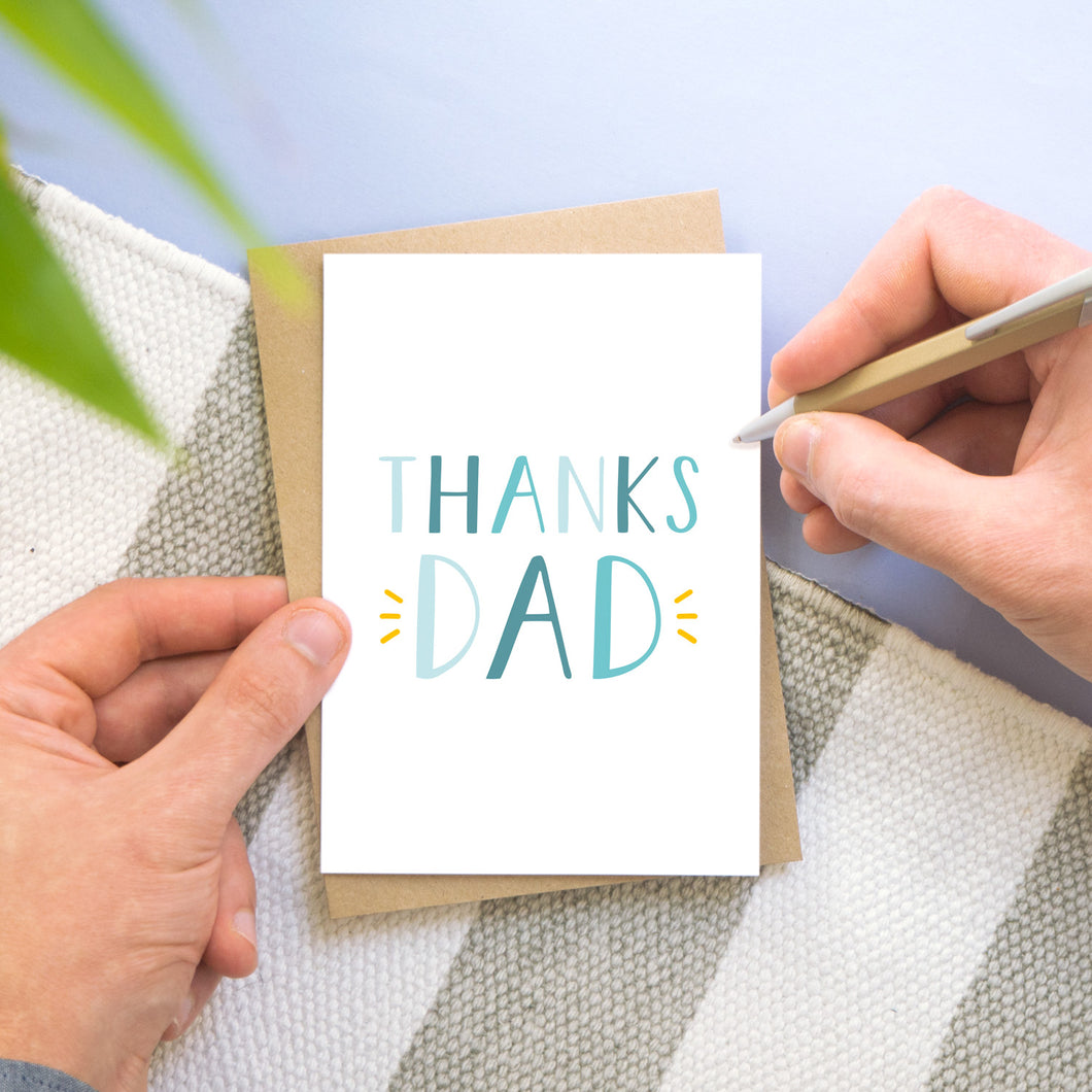 Thanks Dad! A simple typographic card being held by a man on a grey, white and blue background. The text is in varying shades of blue and with a pop of yellow around the word 'dad'.