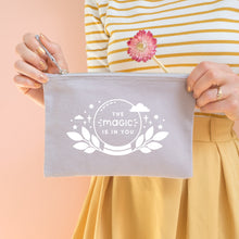 Load image into Gallery viewer, The magic is in you cotton accessory pouch in grey with white text and crystal ball. Photographed on a peach background. Model holds the pouch with a dry flower, wearing a stripy top and yellow skirt.