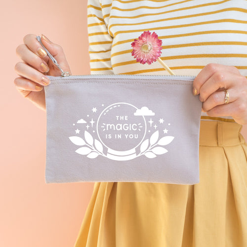 The magic is in you cotton accessory pouch in grey with white text and crystal ball. Photographed on a peach background. Model holds the pouch with a dry flower, wearing a stripy top and yellow skirt.