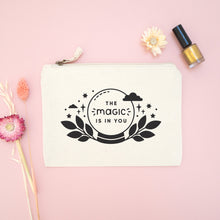 Load image into Gallery viewer, The magic is in you cotton accessory bag in natural with black text and crystal ball. Photographed on a pink background with dried flowers and gold nail varnish.