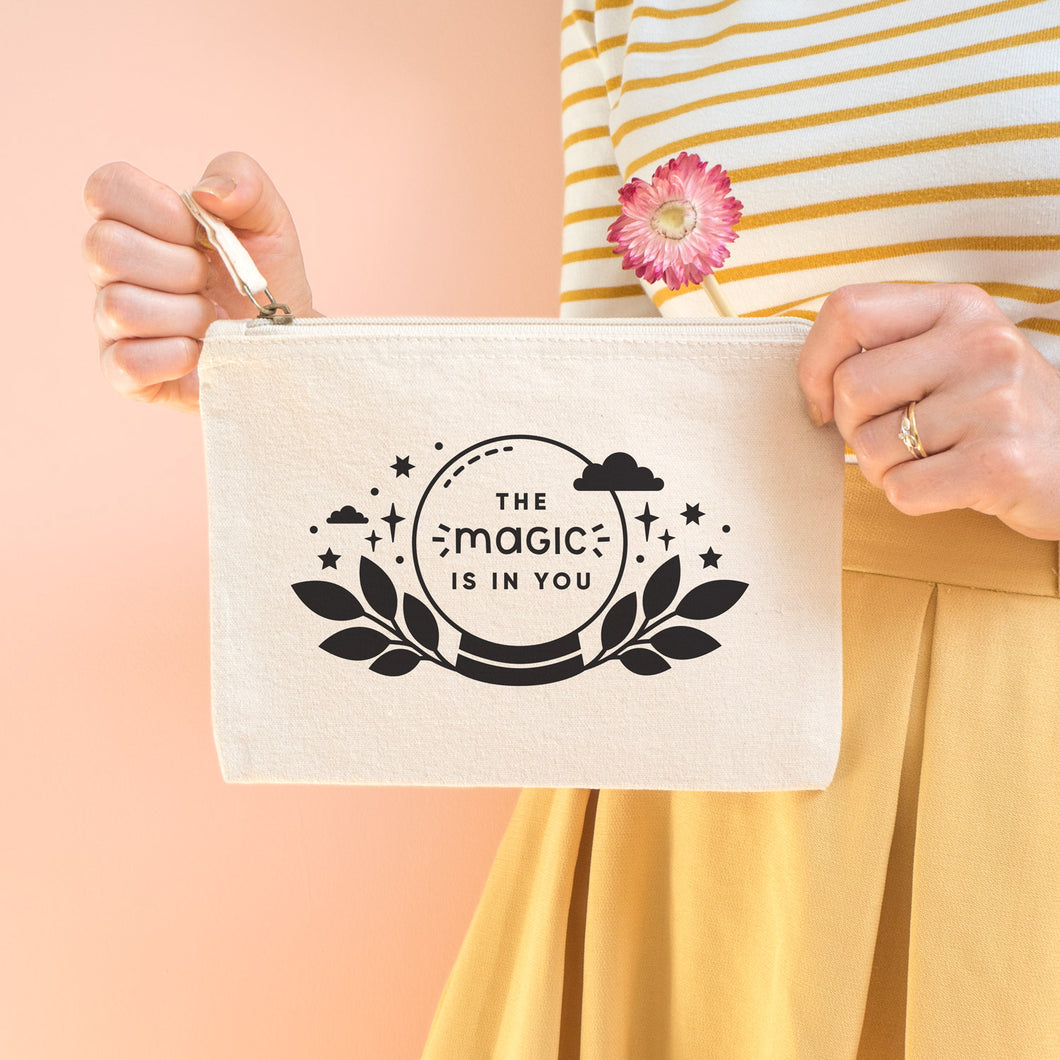 The magic is in you cotton accessory pouch in natural with black text and crystal ball. Photographed on a peach background. Model holds the pouch with a dry flower, wearing a stripy top and yellow skirt.