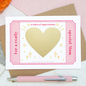 A token of appreciation scratch card by Joanne Hawker featuring a pink token and the words 'for a really special mum'. In the centre is a gold heart before it is scratched off to reveal the message.