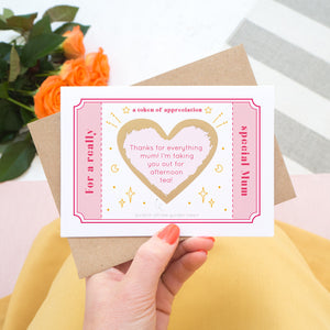 The token of appreciation scratch card showing you an example of a personalised message. The card is shot being held over a pink skirt with roses in the background. The card is pink, red and gold in colour.