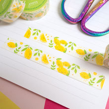 Load image into Gallery viewer, Slices of lemon washi tape that has been cut down and stuck inside of a notebook.