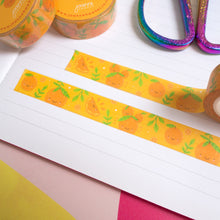 Load image into Gallery viewer, Strips of satsuma washi tape cut to size and stuck down in a white lined notebook.
