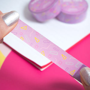 Purple confetti washi tape being peeled from the roll by a pair of hands over a white notebook and pink background.