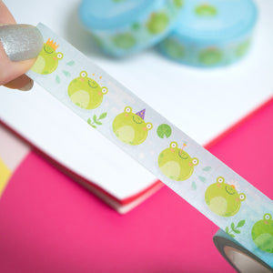 Kawaii frog themed washi tape being peeled from the roll by a pair of hands over a white notebook and pink background.