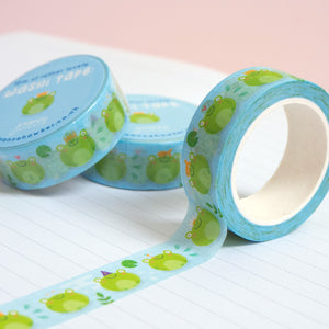 A roll of cute frog washi tape unravelling on a notebook with stacks of paper tape in the background.